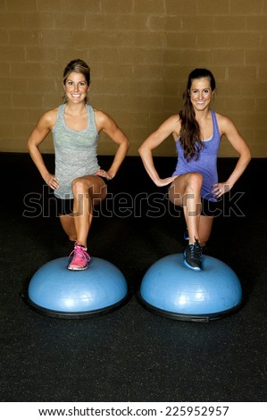 Two athletic female trainers do a front lunge on a bosu ball in a gym. - stock photo
