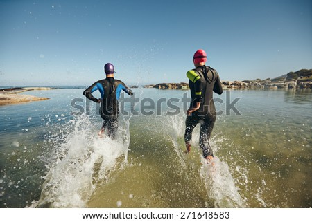 Two athletic swimmers entering the water with their wetsuits on.  Competitors in wet suits running into the water at the start of a triathlon. - stock photo