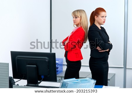 Two attractive business woman in office angry to each other - stock photo