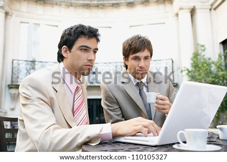 Two attractive businessmen having a meeting while having coffee in a coffee shop's terrace, outdoors. - stock photo