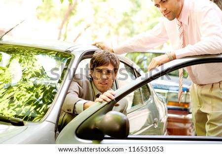 Two attractive businessmen with a smart car in a leafy street, outdoors. - stock photo