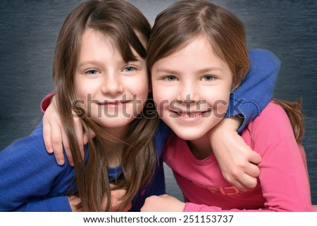 Two attractive cute little girl friends smiling at the camera having put their arms around each others neck over a gray background - stock photo