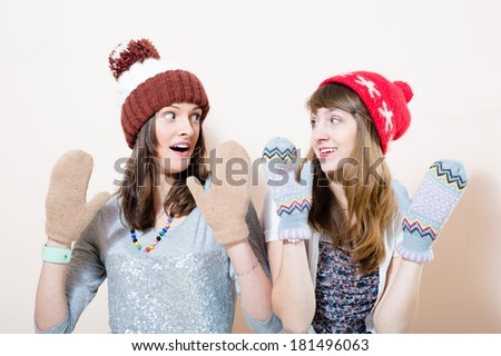 Two attractive funny young women girl friends in winter knit cap and gloves looking at each other on white background - stock photo