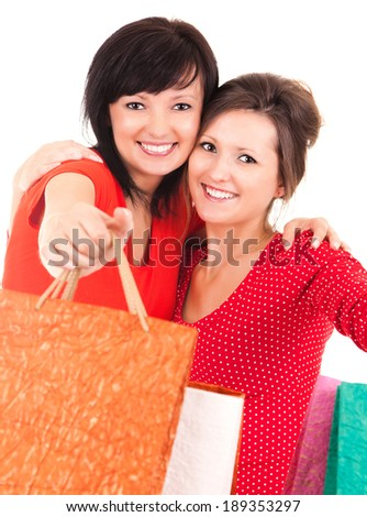 two attractive girl after shopping holding shopping bags, white backgound - stock photo