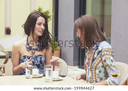 Two attractive girlfriends drinking coffee and talking in the cafe bar - stock photo
