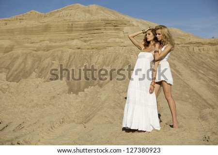 Two attractive girls friends - blond and brunette over sand background - stock photo