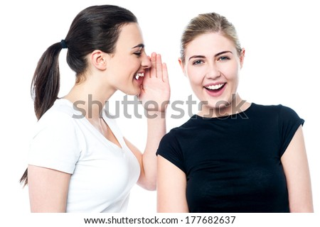 Two attractive girls gossiping isolated on white - stock photo