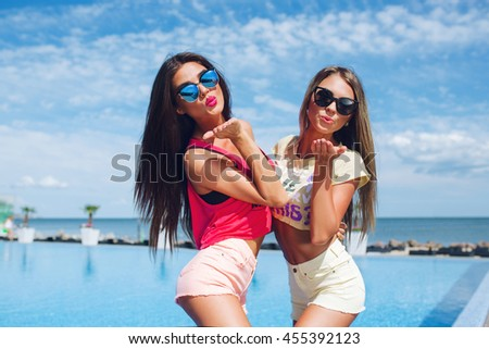 Two attractive girls with long hair are posing near pool on the sun. Brunette girl wears short pink shorts and T-shirt, blond wears yellow shorts and T-shirt. They are sending a kiss to the camera. - stock photo