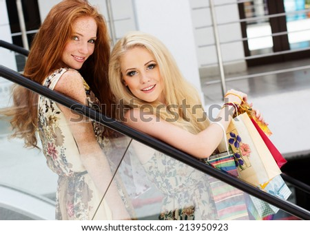 Two attractive happy girls out shopping - stock photo
