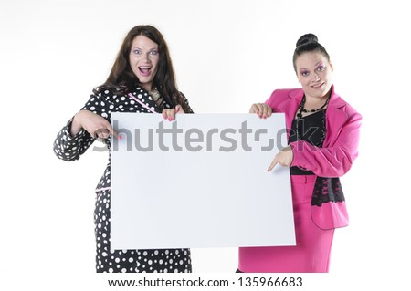Two attractive plus-size models to wear flashy costumes and presenting a blank billboard, isolated against white background. - stock photo