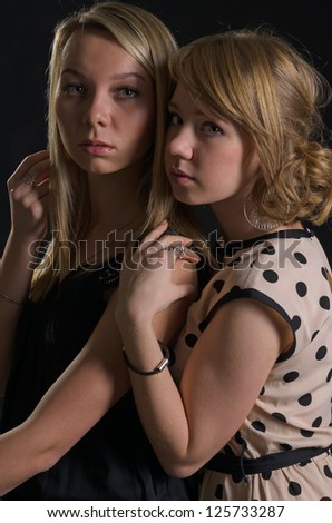 Two attractive scared young women standing close together in the shadows staring at the camera with sombre expressions - stock photo