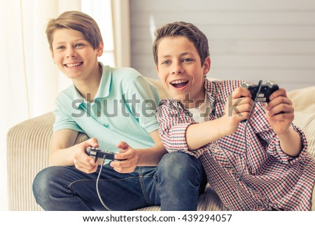 Two attractive teenage boys are playing game console and smiling while sitting on the couch at home - stock photo