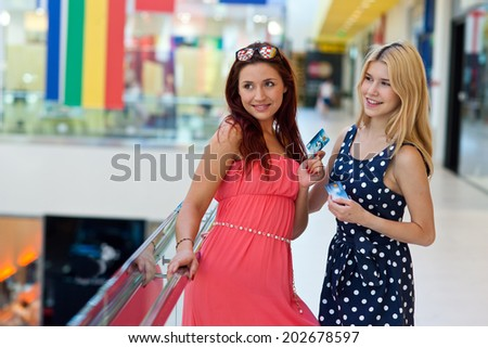 two attractive woman friends with credit cards in shopping mall - stock photo
