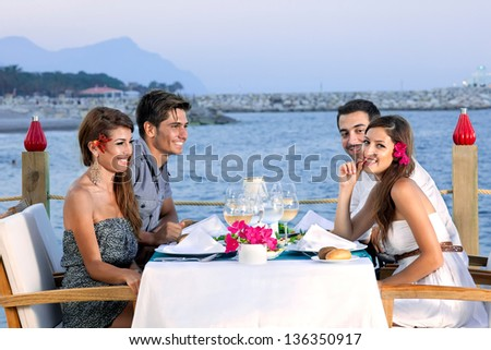 Two attractive young couples celebrating at a seaside restaurant sitting at a table at the waters edge waiting for their meal and enjoying a glass of wine - stock photo