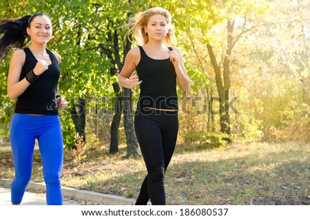 Two attractive young female friends jogging together in a park doing an early morning training workout - stock photo