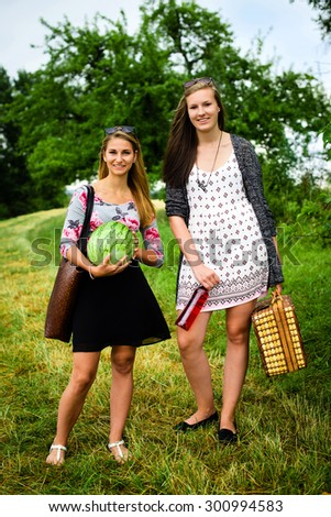 Two attractive young girls are getting ready for a picnic, looking for the right spot - stock photo