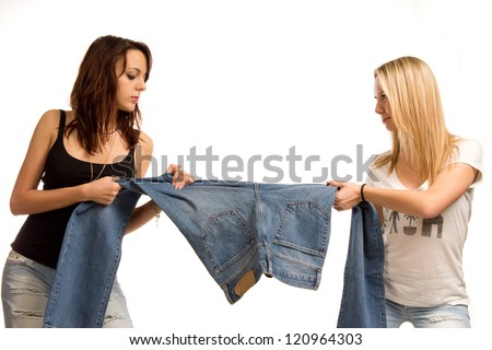 Two attractive young teenage girls standing fighting over jeans each pulling on a leg, half body portrait on white - stock photo