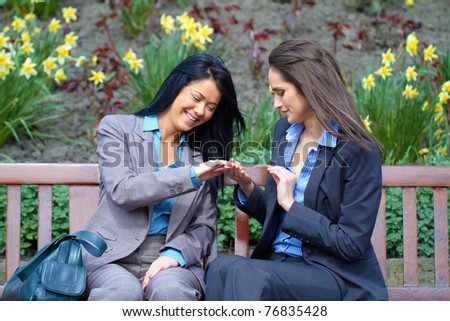 two attractive young woman sits in the park and discuss about nails one of them, outdoor shoot - stock photo