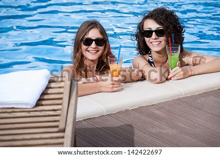 Two attractive young women enjoying swimmer pool and cocktails - stock photo
