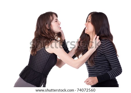 Two attractive young women grabbing each other's hair and appearing to be angry - stock photo