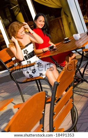 Two attractive young women in street cafe - stock photo