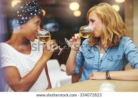 Two attractive young women meeting up in a pub for a glass of white wine sitting at a counter smiling at each other as they sip their glasses - stock photo