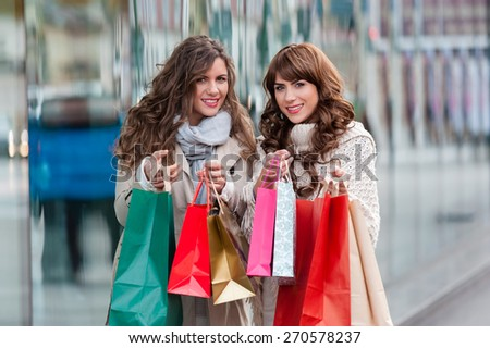 Two attractive young women shopping together,holding shopping bags and gift boxes,smiling while standing in front of shop window. Outdoors. - stock photo