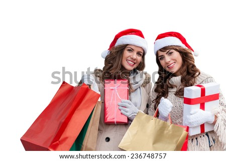 Two attractive young women shopping together,holding shopping bags and gift boxes,with red christmas hat,smiling over isolated white background - stock photo