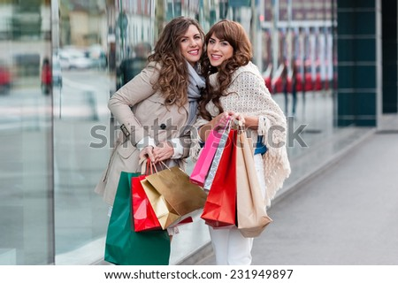 Two attractive young women shopping together,holding shopping bags,smiling, while standing in front of shop window. Outdoors. - stock photo