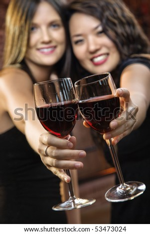 Two attractive young women toasting wine glasses with red wine and smiling. - stock photo