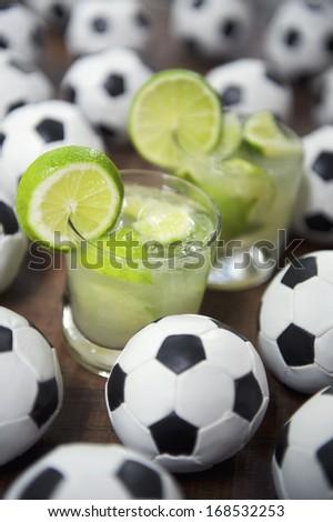 Two authentic fresh lime caipirinhas with soccer footballs Brazilian culture - stock photo