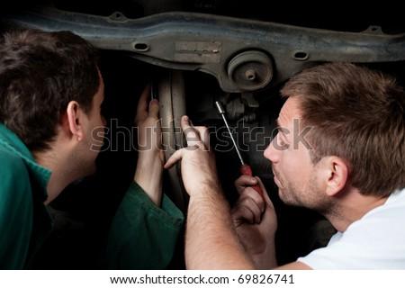Two auto mechanics repair car in auto service - stock photo