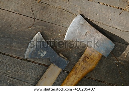 Two axes on a wooden surface - stock photo