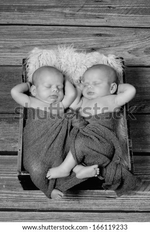 Two babies asleep with their hands tucked under their heads. - stock photo
