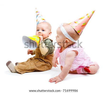 Two babies in party hats, over white - stock photo