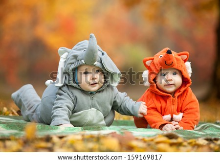 Two baby boys dressed in animal costumes in autumn park, focus on baby in elephant costume - stock photo