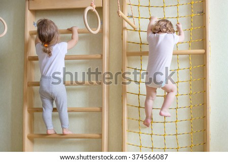 Two baby toddlers climbing up the gymnastic stairs. - stock photo