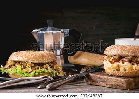 Two Bagels with stew beef, fresh salad, bacon, scrambled eggs and fried onion served on vintage metal tray and wooden chopping board with cup of coffee and coffee pot over wooden table.  - stock photo