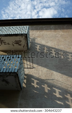 two balconies on the old house and shadows on wall - stock photo