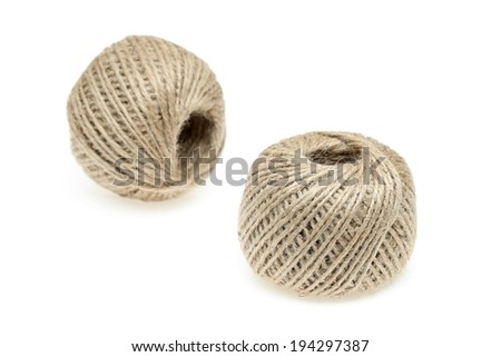 Two balls of beige twine together on a white surface. - stock photo