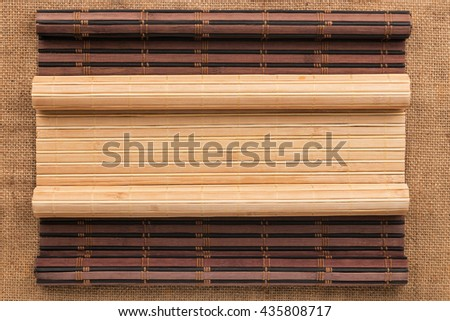 Two bamboo mat twisted in the form of a manuscript on sackcloth, with space for your text - stock photo