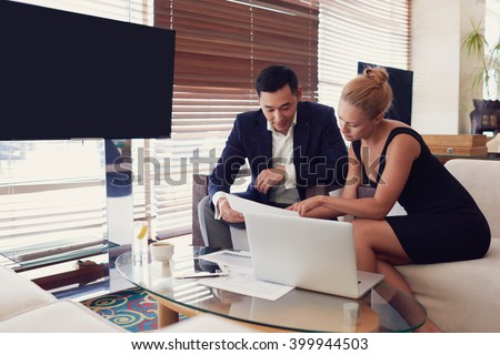 Two bankers are analyzing banking operations by using paper documents with important confidential information and laptop computer, while are sitting in informal atmosphere near screen with copy space - stock photo