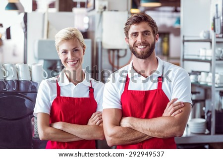 Two baristas smiling at the camera at the cafe - stock photo