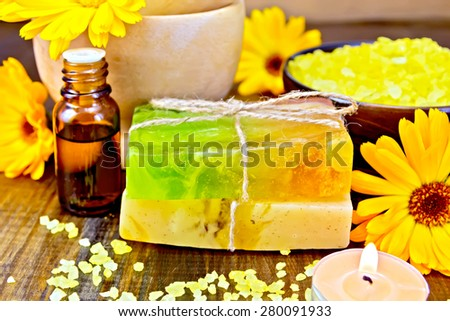 Two bars of homemade soap, yellow bath salt, candle, oil in a bottle and marigold flowers on a background of wooden planks - stock photo