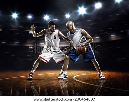 Two basketball players in action in gym - stock photo