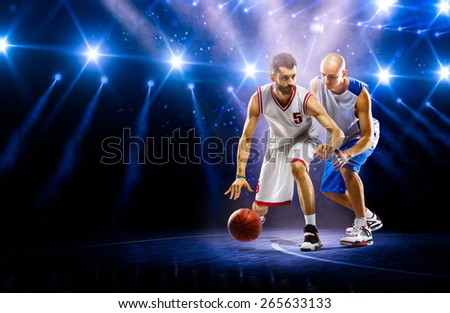 Two basketball players in action on arena in lights - stock photo