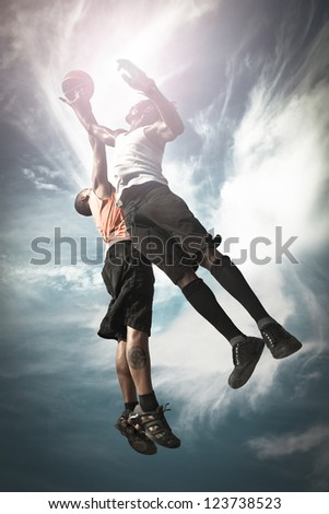Two Basketball players playing street basket and jumping together to catch the ball - stock photo
