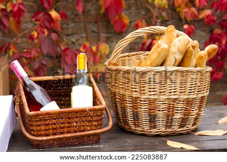 Two baskets with wine and bread in autumn - stock photo