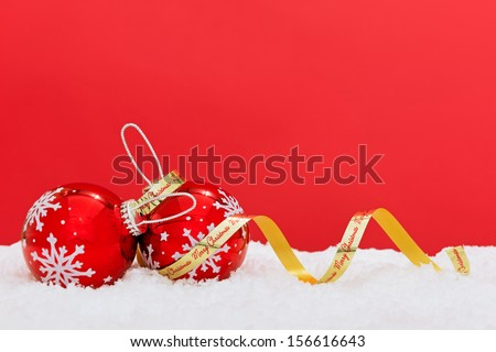 Two baubles with snowflakes and a gold Merry Christmas ribbon on white snow with red background, copy space to add your own text. - stock photo