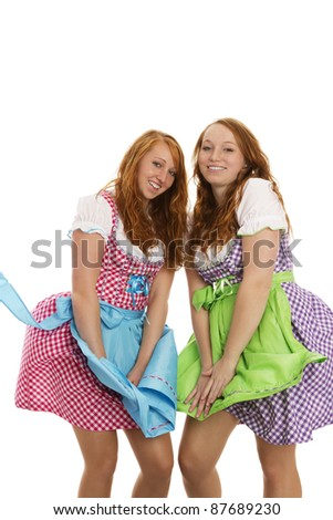 two bavarian dressed girls fighting with wind on white background - stock photo